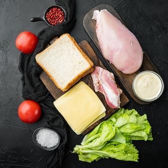 Ingrédients club sandwich, sur fond noir, vue du dessus