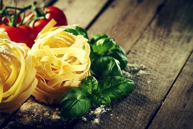 Ingrédients colorés délicieux et frais pour cuisiner des tagliatelles aux pâtes au basilic frais et aux tomates. fond de table en bois.