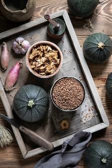 Ingrédients de courgettes rondes farcies aux chanterelles sur boîte en bois