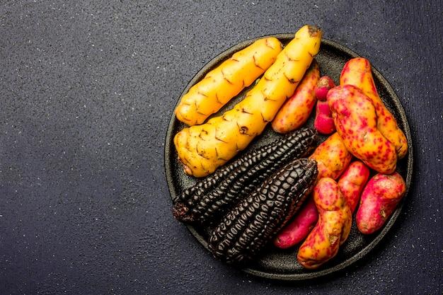 Ingrédients crus péruviens pour la cuisson du maïs noir et des patates douces