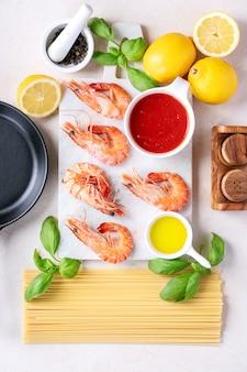 Ingrédients crus pour la cuisson: crevettes crevettes pâtes italiennes spaghetti