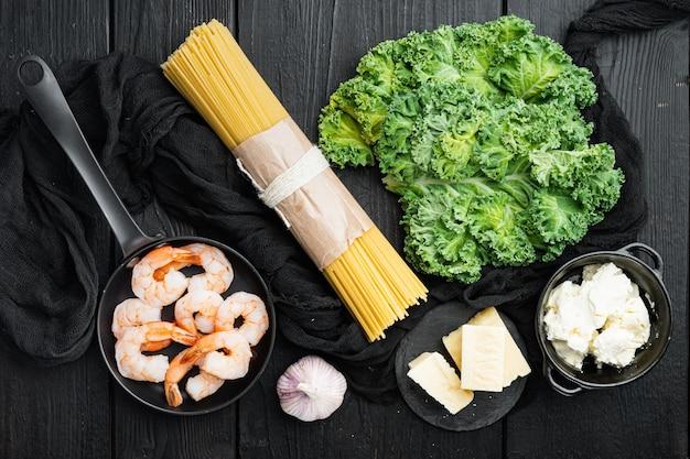 Ingrédients crus pour la cuisson des pâtes vertes aux crevettes avec du parmesan et de la ricotta, sur table en bois noir