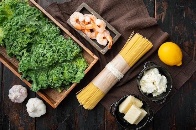 Ingrédients crus pour la cuisson des pâtes vertes aux crevettes avec du parmesan et de la ricotta, sur la vieille table en bois sombre, vue de dessus à plat