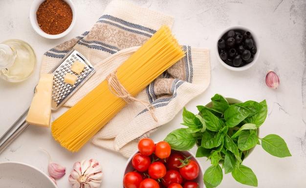 Ingrédients crus pour la cuisson des spaghettis sur une surface blanche
