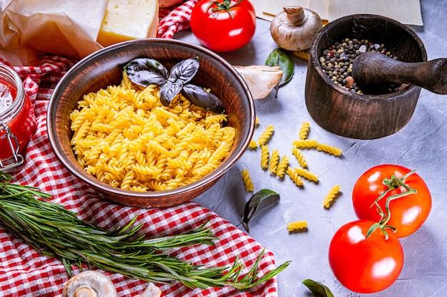 Ingrédients crus pour faire des pâtes italiennes sur une surface grise