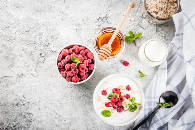 Ingrédients crus pour le petit déjeuner sain d'été, céréales (avoine), framboise fraîche, feuilles de menthe, yaourt, miel, sur béton léger, vue de dessus du fond