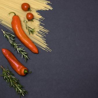 Ingrédients de la cuisine italienne. nature morte de la cuisson des pâtes sur une vue de dessus de fond noir. cuillères en bois avec des épices. cadre de produits et légumes.