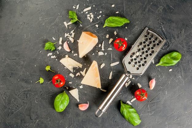 Ingrédients de la cuisine italienne.parman râpé et un morceau, avec une râpe, des feuilles de basilic, de l'ail et des tomates cerises sur une table en béton foncé. copyspace vue de dessus