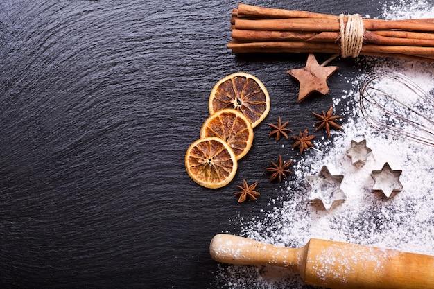 Ingrédients de cuisson de noël étoiles d'anis et bâtons de cannelle sur fond sombre