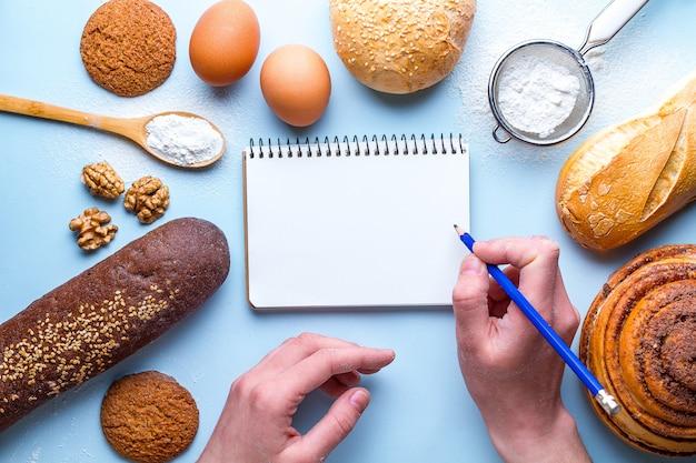 Ingrédients de cuisson pour la farine et les produits de boulangerie de seigle. pain frais, baguette, brioches et livre de recettes ouvert sur fond bleu.