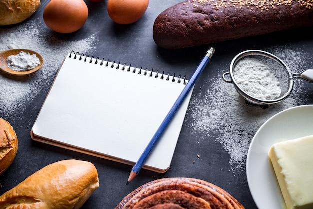 Ingrédients de cuisson pour la farine et les produits de boulangerie de seigle. pain frais, baguette, brioches et livre de recettes ouvert sur un fond de tableau noir