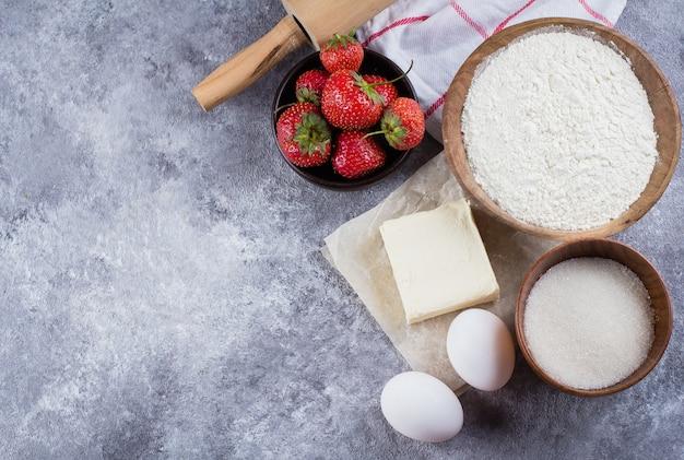 Ingrédients de cuisson pour gâteaux, tartes, sablés: farine, œufs, sucre, beurre, rouleau à pâtisserie