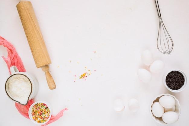 Ingrédients de cuisson près du fouet et du rouleau à pâtisserie