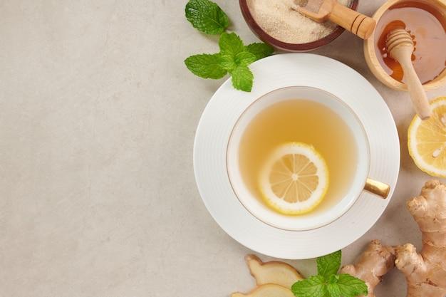 Ingrédients du thé au gingembre, thé réconfortant et chauffant sain sous recette simple. thé au gingembre et ingrédients - citron, miel.vue de dessus. mise à plat. fraîchement du jardin biologique de croissance à domicile. concept de nourriture.