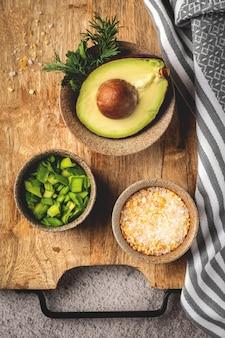 Ingrédients et épices pour cuisiner sur une planche de bois: avocat, herbes, oignons, sel, vue de dessus
