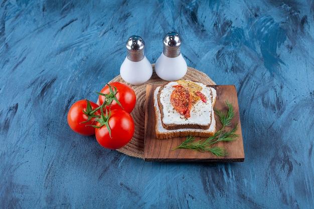 Ingrédients frais du sandwich sur une planche, sur le fond bleu.