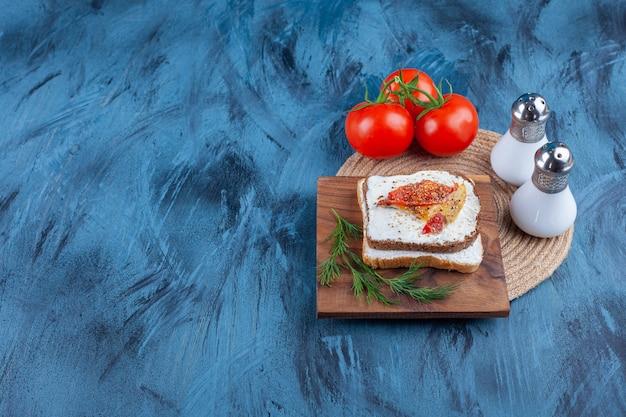 Ingrédients frais du sandwich sur une planche, sur la table bleue.