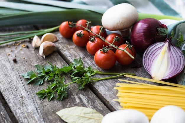 Ingrédients frais pour la cuisson des pâtes, tomates et épices sur table en bois avec copie espace