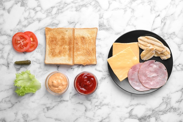 Ingrédients frais pour un délicieux sandwich sur fond de marbre blanc, mise à plat