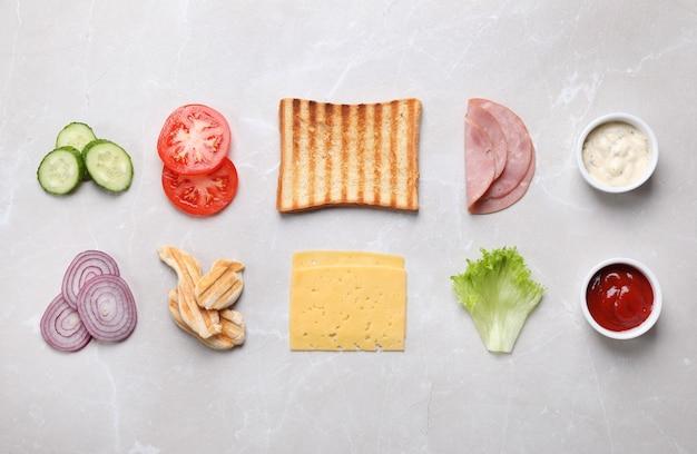 Ingrédients frais pour un délicieux sandwich sur fond de marbre gris, mise à plat