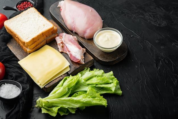 Ingrédients frais pour un délicieux sandwich, sur fond noir avec espace de copie pour le texte