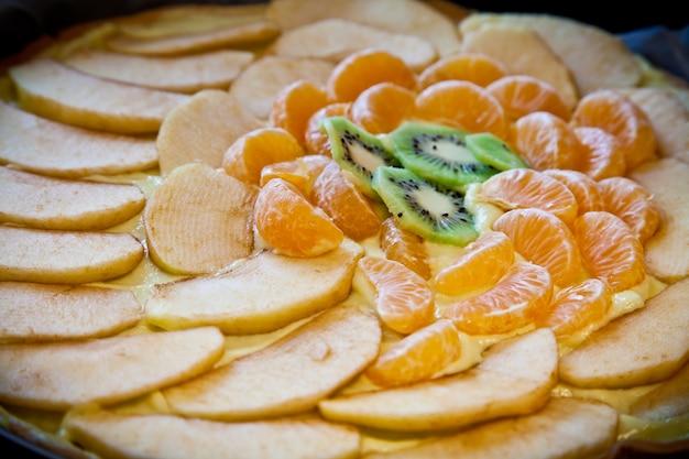 Ingrédients frais prêts pour un gâteau aux fruits : kiwi, pomme et mandarine