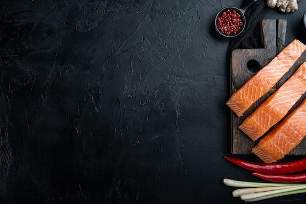 Ingrédients de gâteaux de poisson aux herbes et épices de saumon, sur fond texturé noir, à plat avec un espace pour le texte