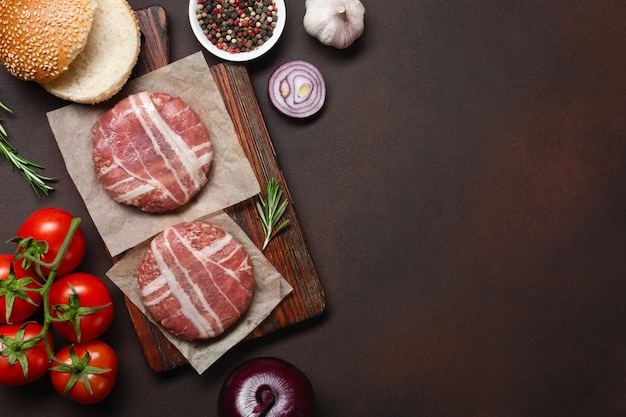 Ingrédients hamburger crue côtelette, tomates, laitue, pain, fromage, concombres et oignons sur fond rouillé