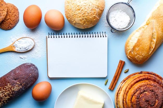 Ingrédients et livre de recettes pour la cuisson de la farine et des produits de boulangerie de seigle. pain frais, baguette et brioches sur fond bleu.