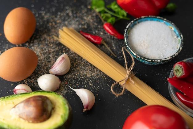 Ingrédients naturels pour la cuisson des pâtes, spaghettis crus attachés avec une corde, sel et poivre sur les tables