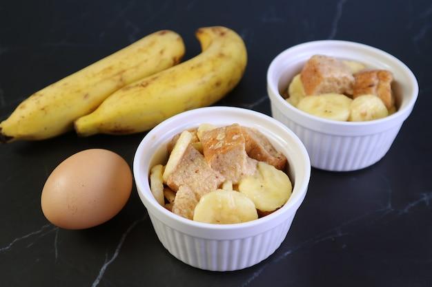 Ingrédients non cuits prêts pour la cuisson du pouding au pain aux bananes dans un petit bol en céramique