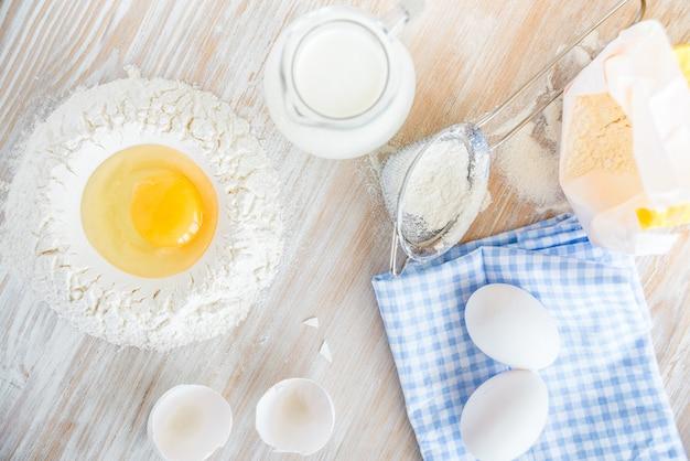 Ingrédients et outils pour la cuisson - farine, œufs et verre de lait sur la table rustique en bois. préparation de pâtes maison