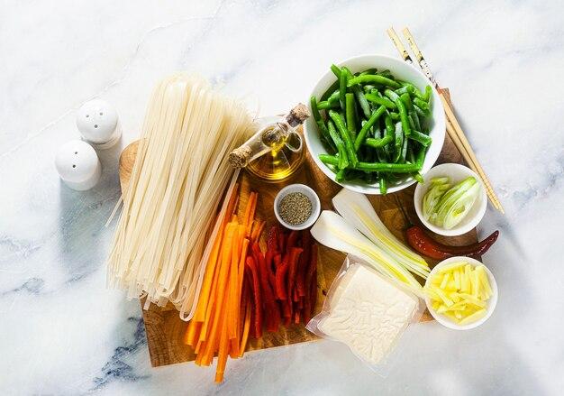 Ingrédients pad thai sur une planche à découper sur une table en marbre blanc