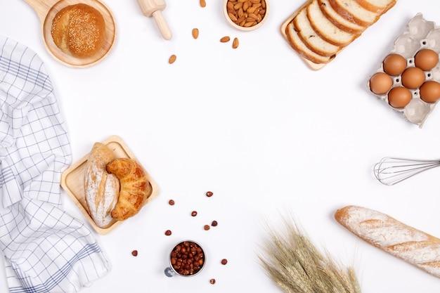 Ingrédients de pains faits maison, farine, noix d'amande, noisettes, oeufs sur fond blanc.