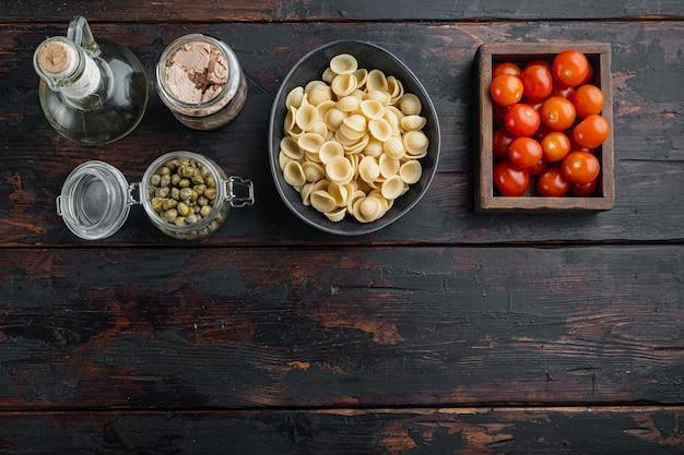 Ingrédients de pâtes au thon à la semoule de blé dur, sur fond de bois foncé, mise à plat avec espace de copie pour le texte