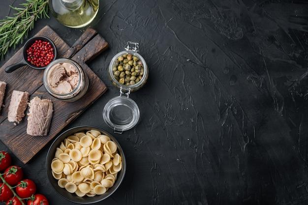 Ingrédients de pâtes au thon sicilien sur fond noir, plat