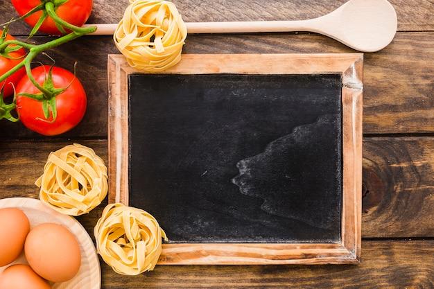 Ingrédients de pâtes et cuillère près de tableau noir
