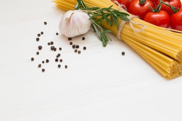 Ingrédients de pâtes italiennes sur table en bois blanc, tomates, ail, romarin, poivre, espace copie macro