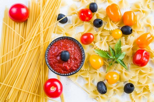 Ingrédients de pâtes, pâtes crues, tomates cerises, olives et feuilles de basilic sur fond blanc