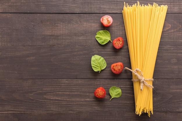 Ingrédients de pâtes. tomate sur le fond en bois