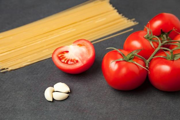 Ingrédients de pâtes. tomates, pâtes à spaghetti, ail et tomates sur fond grunge sombre. orienté vers l'horizon