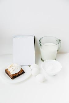Ingrédients avec pâtisserie et bloc-notes en spirale sur fond blanc