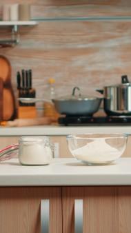 Ingrédients de pâtisserie pour gâteaux et pain faits maison dans une cuisine vide. salle à manger moderne équipée d'ustensiles prêts à cuisiner avec de la farine de blé dans un bol en verre et des œufs frais sur la table