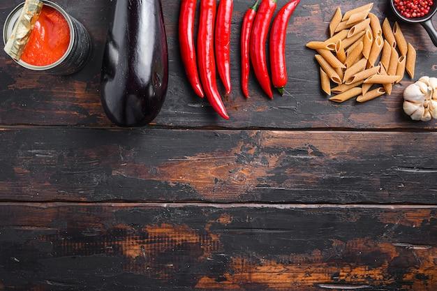Ingrédients penne aux aubergines pâtes aux aubergines, sauce tomate au poivre, sur un ancien espace de vue de dessus de table en bois pour le texte.