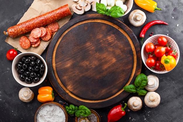 Ingrédients de la pizza sur fond sombre et planche à découper ronde. pepperoni, mozzarella, tomates, olives, champignons et farine sont des produits différents pour faire des pizzas et des pâtes