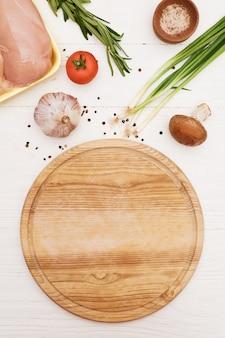 Ingrédients et planche à découper ronde. filet de poulet, tomate, oignons verts, champignons, ail, romarin. vue d'en-haut.
