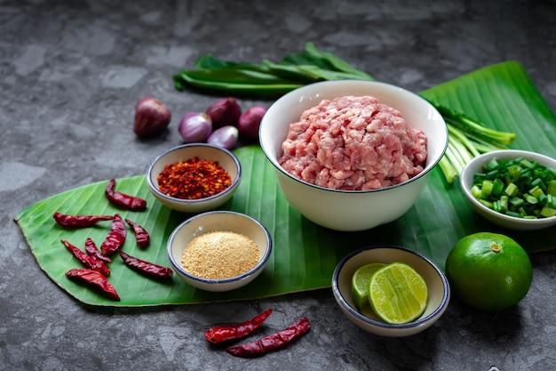 Ingrédients de porc haché épicé sur feuille de bananier