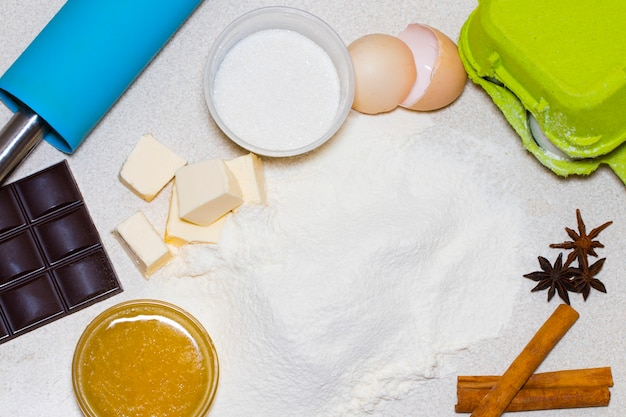 Ingrédients pour les biscuits de noël faits maison. ingrédients de la recette de la pâte (œufs, farine, beurre, sucre) sur la table vue du haut.