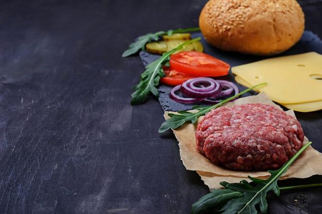 Ingrédients pour burger: côtelette crue, tomate, fromage, oignon