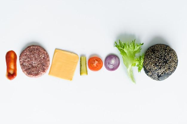 Ingrédients pour le burger noir sur fond blanc.